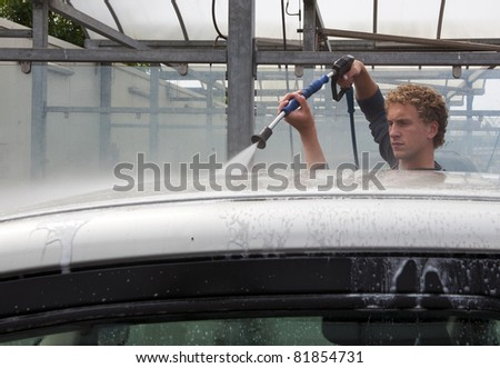 Man washing his car with a high pressure water jet - stock photo