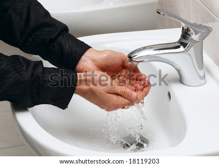 Man washing his hands in running water, in a public toilet. - stock photo