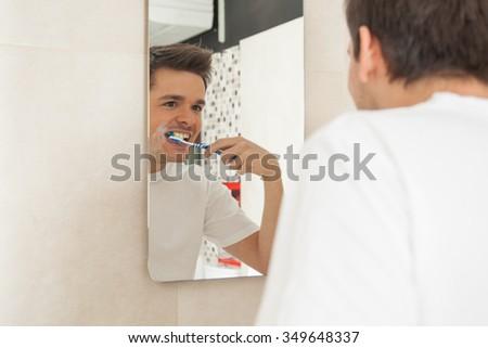 Man washing his teeth - stock photo