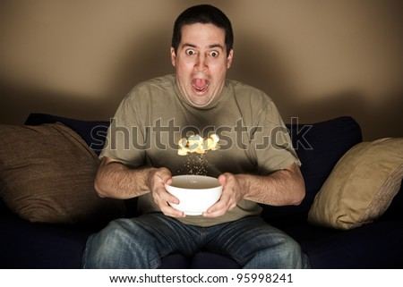 Man watching a horror movie jumps in shock - stock photo