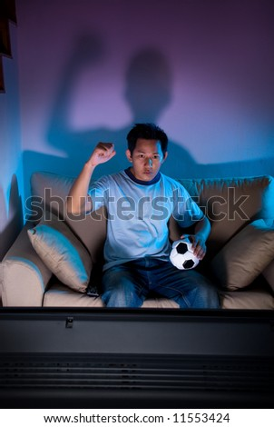 Man watching live football on television - stock photo