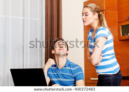 Man watching something on laptop, his wife trying to look what he doing - stock photo