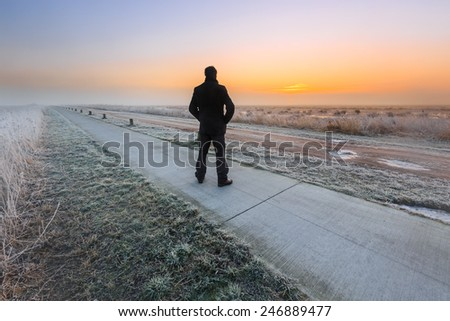 Man watching the sunrise on a cold winter day in Holland - stock photo