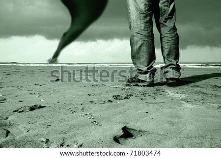 man watching the tornado on the beach - stock photo