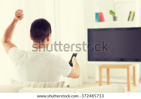 man watching tv and supporting team at home - stock photo