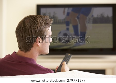 Man Watching Widescreen TV At Home - stock photo