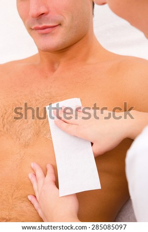 Man waxing his chest hair - stock photo