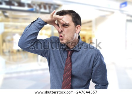 Man wearing a blue shirt and red tie. He is grabbing his nose - stock photo