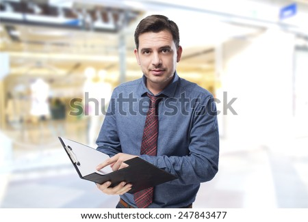Man wearing a blue shirt and red tie. He is holding a black folder - stock photo