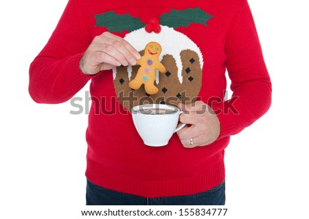 Man wearing a Christmas jumper about to dip a gingerbread man in a cup of hot chocolate, isolated against a white background. - stock photo