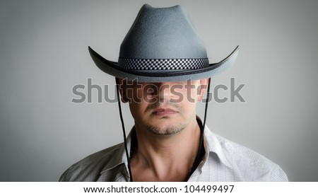 Man wearing a cowboy hat that is too big for him; covering his eyes - stock photo