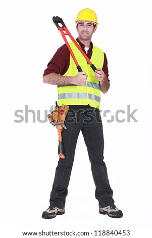 Man wearing a hard hat and holding large clippers - stock photo