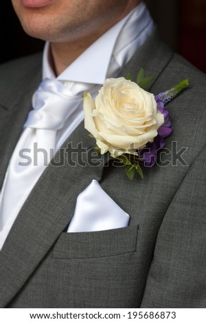 man wearing a rose buttonhole wedding flowers - stock photo