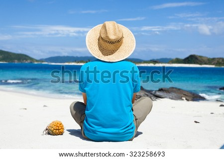 Man wearing a straw hat, sitting on a deserted tropical island beach, Zamami Island of the Kerama Islands National Park, Okinawa, Japan - stock photo
