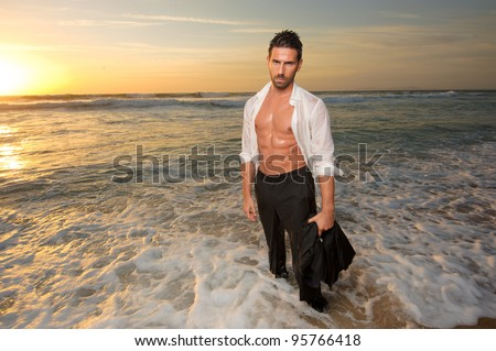 man wearing a suit all wet on the sea at the beach - stock photo