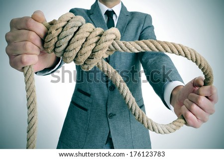 man wearing a suit holding a rope with a hangmans noose - stock photo