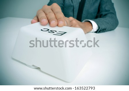 man wearing a suit sitting in a table pressing a giant escape key with his hand - stock photo
