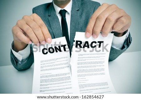 man wearing a suit sitting in a table ripping up a contract - stock photo