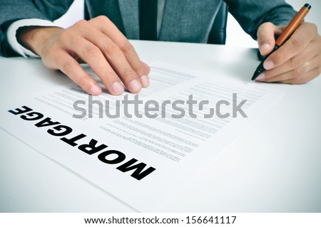 man wearing a suit sitting in a table signing mortgage loan contract - stock photo
