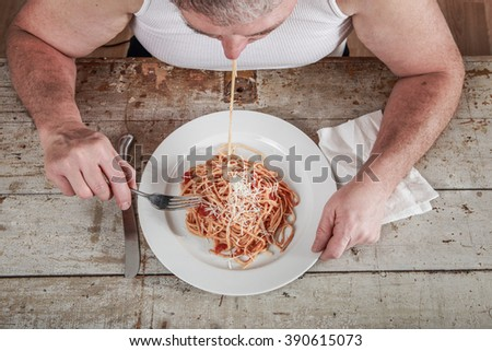 Man wearing an undershirt eating spaghetti, overeating adult. - stock photo