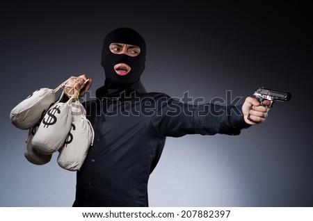 Man wearing balaclava with gun - stock photo