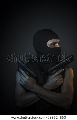 Man wearing balaclavas and bulletproof vest with firearms - stock photo
