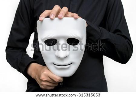 Man wearing black shirt holding a white mask with white background. - stock photo