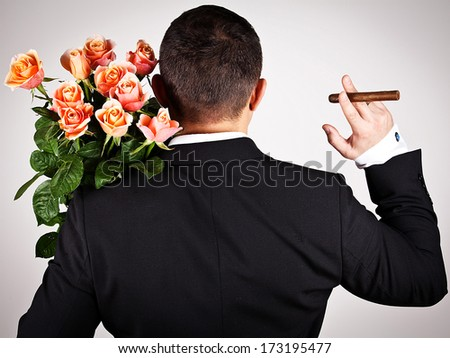 Man wearing black suit hiding a bouquet of flowers behind his back. Valentines day.  - stock photo