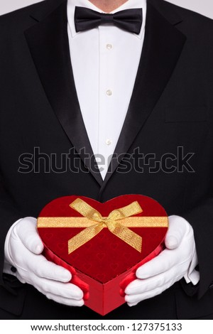 Man wearing black tie and white gloves holding a red heart shaped box of chocolates. - stock photo