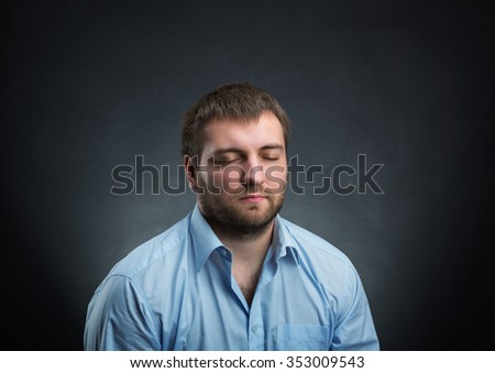 Man wearing blue shirt dreaming with closed eyes over black - stock photo