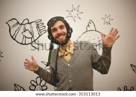 man wearing in pilot helmet, moved apart his hands  - stock photo