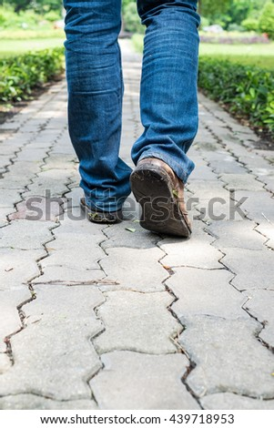 Man wearing jeans and old brown leather shoes walking on the path to the park or garden - stock photo