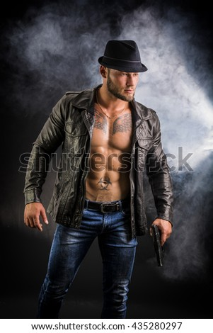 Man wearing leather jacket on naked muscular torso - stock photo