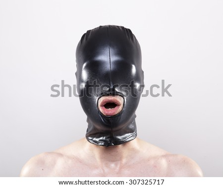 Man wearing mask without openings for his eyes opening his mouth - stock photo