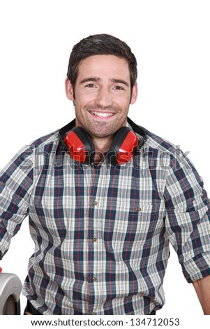 Man wearing protecting ear muffs - stock photo