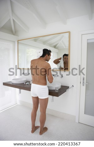 Man wearing underwear and drying hair in bathroom - stock photo