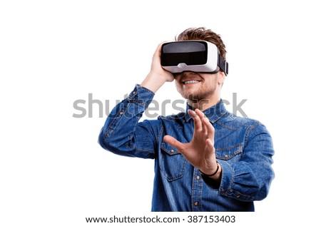 Man wearing virtual reality goggles. Studio shot, white backgrou - stock photo