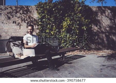 Man wearing white tshirt sitting city park and reading book. Studying at the University, preparation for exams. Books, laptop, backpack bench. Horizontal,  film effect - stock photo