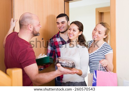 Man welcomes smiling friends at home - stock photo