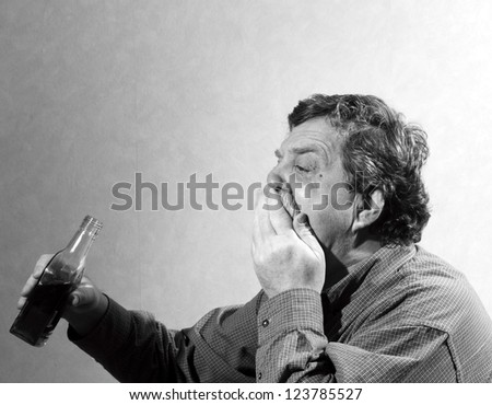 man wipes his mouth and holding a bottle of whiskey - stock photo