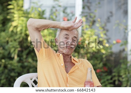 Man wiping sweat from his forehead - stock photo