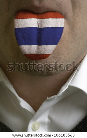 man wit open mouth spreading tongue colored in thailand flag as symbol of values like teaching, learning, multilingual speaking different of languages - stock photo