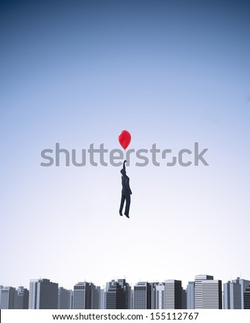 Man with a balloon floating above a city  - stock photo
