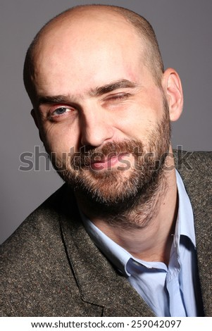 man with a beard, hair loss, winking  - stock photo