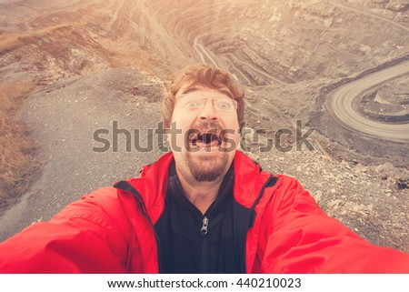 Man with a beard in a red jacket and glasses falls on stones and frightened shouts. Toned - stock photo