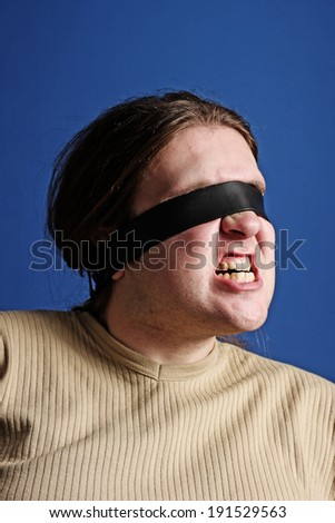 Man with a belt over his eyes - stock photo
