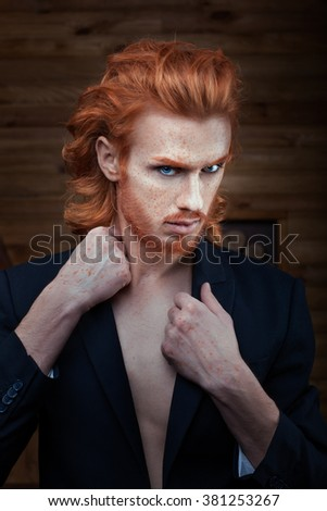 Man with a bright fiery hair dressed in a jacket on a naked body. - stock photo