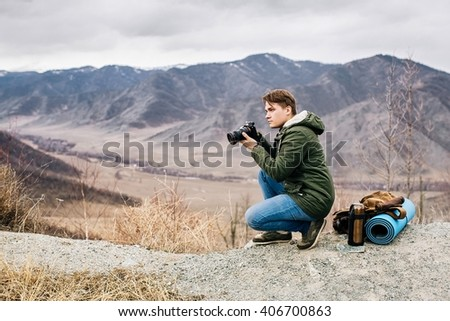 man with a camera on the background of mountain valley - stock photo