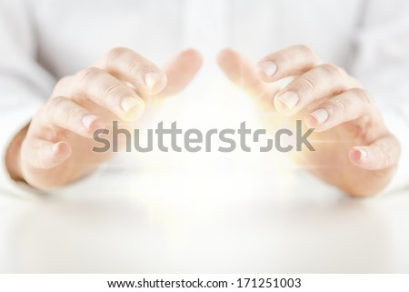Man with a glowing crystal ball holding his hands protectively above it to feel the energy as he foretells or predicts the future conceptual of a fortune teller, soothsayer, mystic or clairvoyant - stock photo