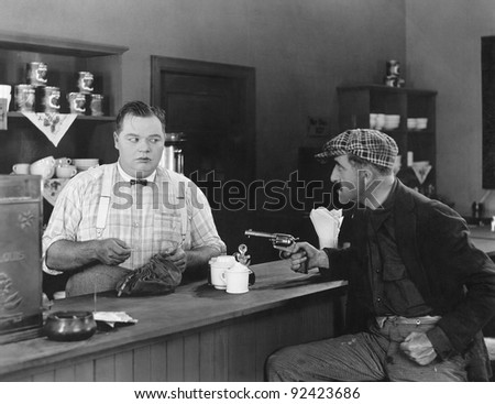 Man with a gun holding up a diner owner - stock photo